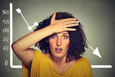 Stressed shocked woman with financial market chart graphic going down on grey office wall background. Poor economy concept. Face expression, emotion, reaction